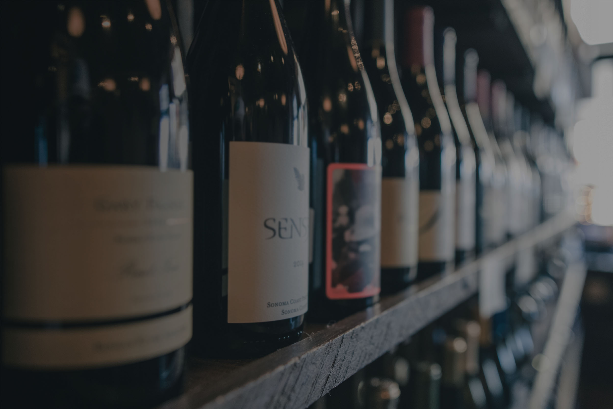 Blurry image of bottles of wine on a shelf