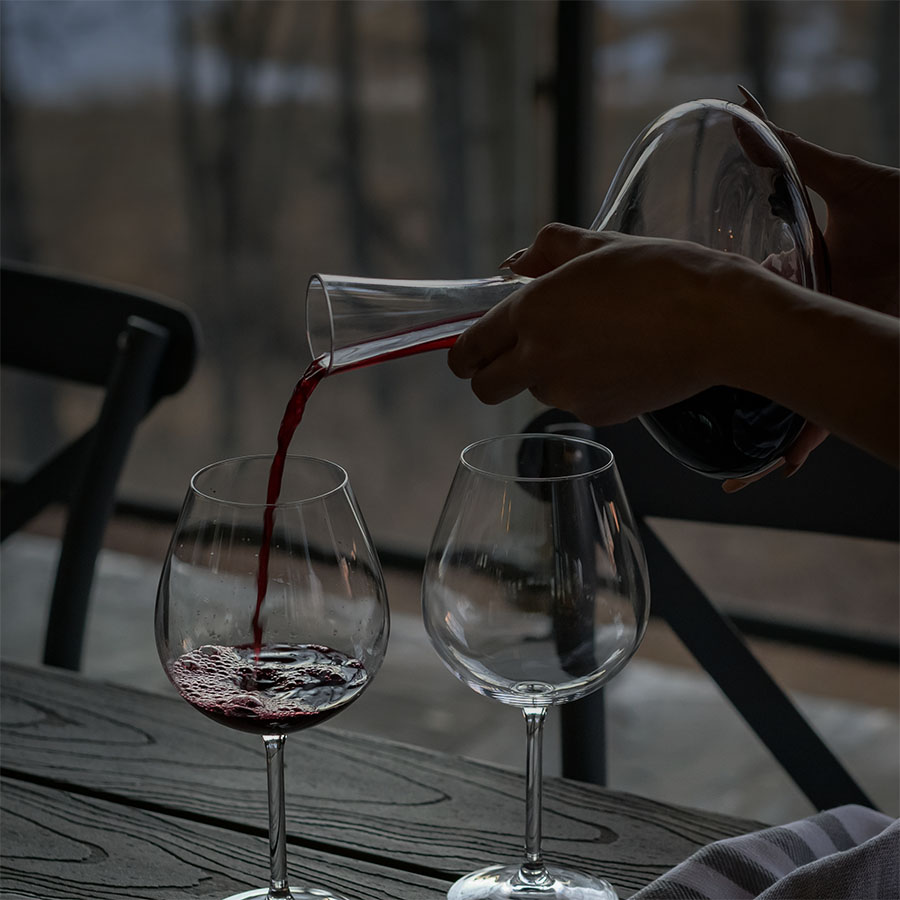 Red wine being poured into a glass from a decanter