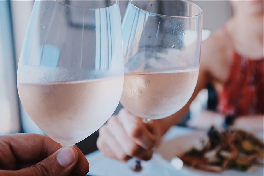Two people doing a cheers with glasses of rosé