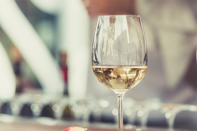 A glass of white wine with a blurry background